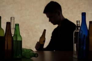 Young man drinking from bottles may have alcohol use disorder